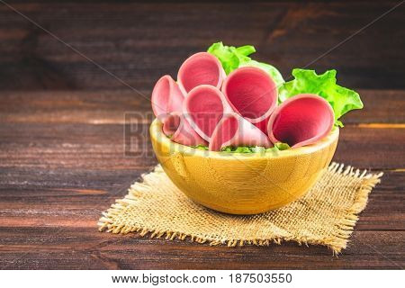 Sliced Sausage With Lettuce In A Wooden Plate. Gray Background.