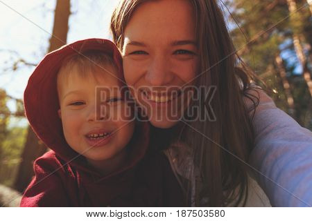Happy smiling mother and child playing together in park. Little boy and mom having fun, looking at camera. Happy family concept.