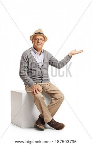 Senior sitting on a cube and gesturing with his hand isolated on white background