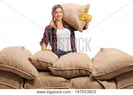 Female farmer behind a pile of burlap sacks looking at the camera and smiling isolated on white background