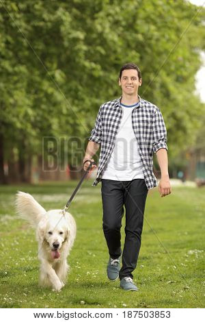 Full length portrait of a young man with a dog walking towards the camera in a park