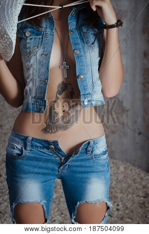 photo of girl in denim clothing. Nude breast