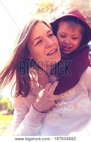 Emotional Portrait of smiling mother and son playing together in park. Little son hugging his young mom, having fun together. Happy family concept.