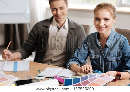 Color palette. Pleasant beautiful delighted woman holding pieces of paper and smiling while working with her colleague