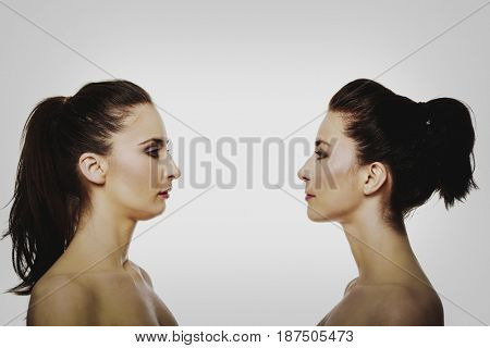 Two sisters standing face to face.