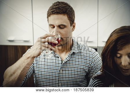 Man with his wineglass in the kitchen.