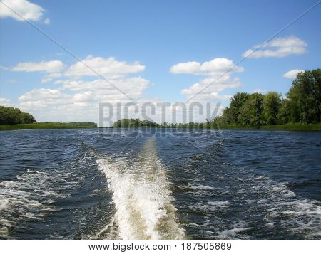 Landscape with a river behind the boat. A Wake on the water. Summer, Sunny day.
