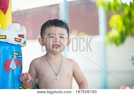 Asian Kid Playing In Inflatable Baby Swimming Pool On Hot Summer Day.
