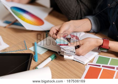 Creative workspace. Close up of a pieces of paper being held by a nice professional female designer while sitting at the table