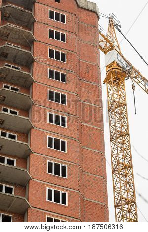 The construction of multi-storey houses of red brick. Crane