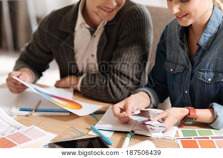 Creative designers. Positive delighted attractive woman holding pieces of paper and smiling while sitting with her colleague