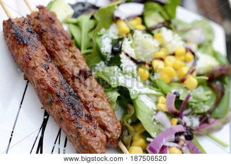 Lamb kebab with mixed salad on a white plate