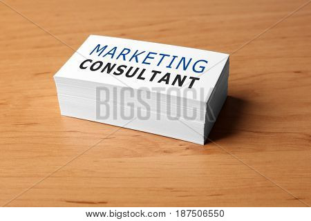 Stack of business cards on wooden background. Marketing consultant concept