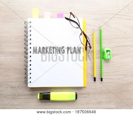 Marketing plan concept. Office stationery on wooden background