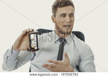 Talking businessman holding hourglass.