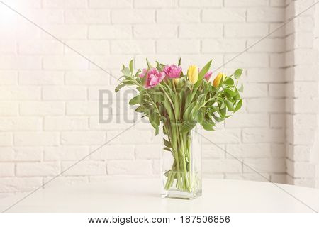 Vase with bouquet of beautiful tulips on table against brick wall background
