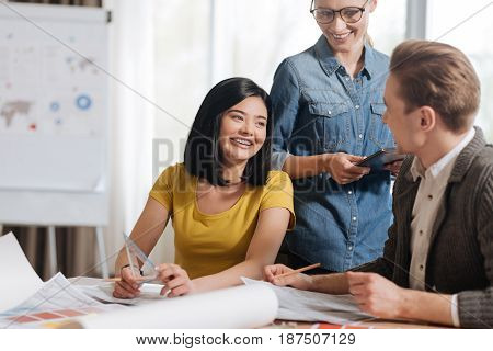 Pleasant work. Joyful delighted attractive woman holding smiling and looking at her colleague while holding a ruler