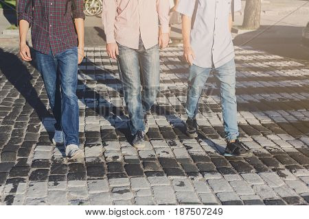 Walk in city center. Three unrecognizable man crossing the crosswalk, copy space for text