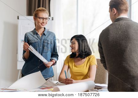 What do you think. Joyful attractive nice woman standing in front of her colleagues and showing them a sketch while asking their opinion about it