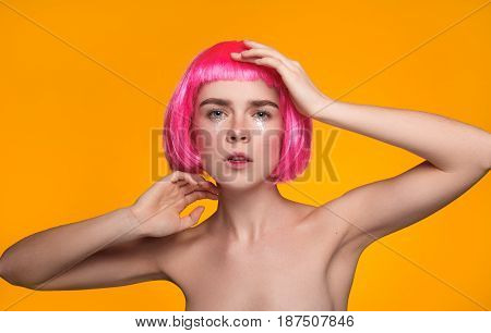 Sensual young model posing nude in pink wig on yellow background.