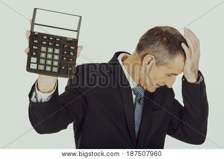Depressed businessman holding a calculator