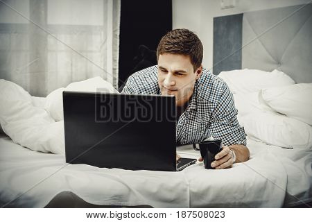 Casual young man using laptop in bed at home.