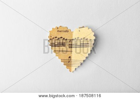Paper heart with notes on white background, music concept