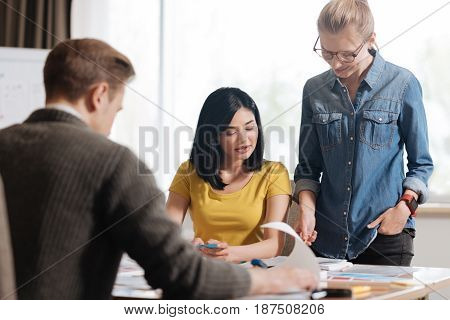 At work. Nice pleasant beautiful woman standing woman standing near her colleague and looking at the notebook while being at work