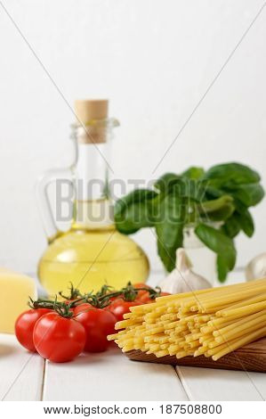 Culinary Still Life With Dry Pasta Bucatini, Fresh Tomatoes And Basil, Bottle Of Oil On Light Backgr