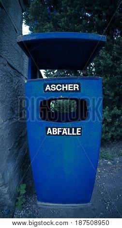 Trash bin with the German words for ashtray and waste bin