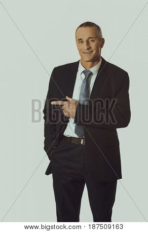Mature businessman pointing to the left