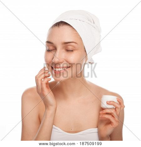 Cheerful woman with eyes closed applying the cosmetic cream on her face isolated on white.