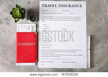 Passport with ticket and pen near blank travel insurance form on grey background