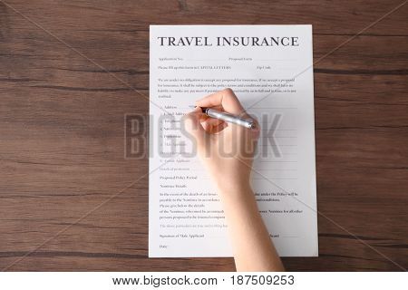 Female hand holding pen and filling in blank travel insurance form on wooden background