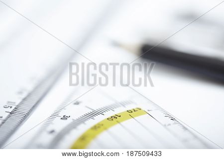 Drawing tools on a paper. Extremely close-up photo with shallow depth of field. Focus on ruler