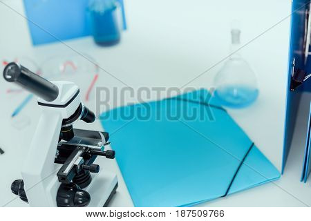 Folder, Tube With Blue Reagent And Microscope On Tabletop In Chemical Lab