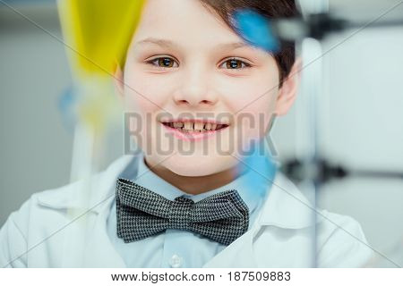 Close-up Portrait Of Cute Smiling Schoolboy In Lab Coat Looking At Camera, Science School Concept