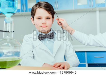 Cropped Shot Of Little Scientist With Tweezers Taking Hair Sample From Boy In White Coat Sitting In