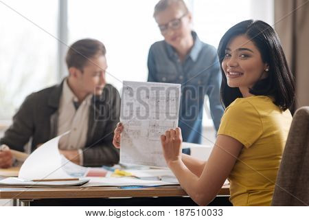 Professional engineers. Joyful positive nice woman holding an engineering drawing and showing it to you while being at work