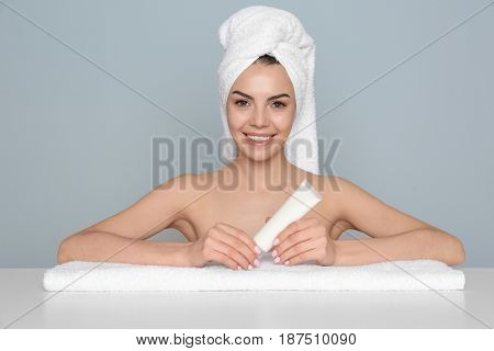 Beautiful young woman after bath with cream on color background
