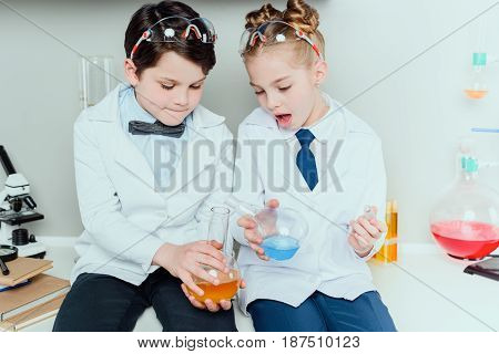 Schoolchildren In White Coats Holding Reagents In Flasks Sitting In Science Laboratory