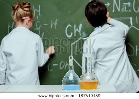 Back View Of Boy And Girl In Lab Coats Drawing Chemical Formulas On Chalkboard, Science School Conce