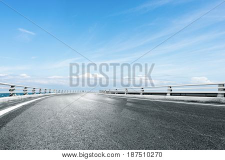 empty road by blue sea in blue sunny sky