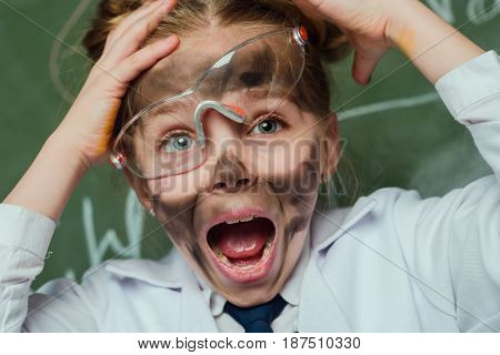 Portrait Of Shocked Girl In Lab Coat And Protective Glasses