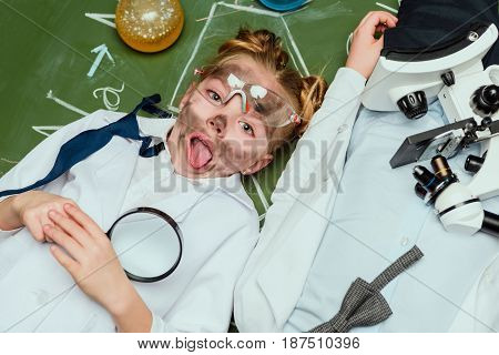 Elevated View Of Girl With Magnifying Glass Lying On Chalkboard With Friend Near By
