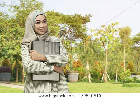 Beautiful Asian Muslim Woman With Smiley Face Holding Laptop