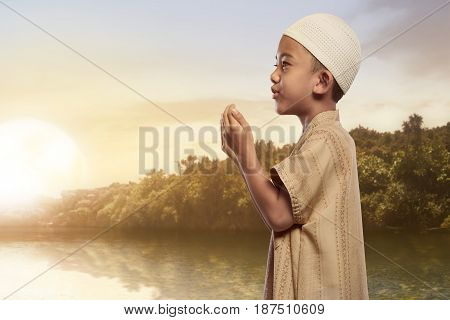 Asian Muslim Boy With Traditional Dress Praying