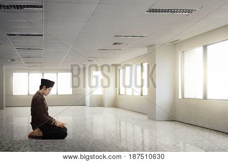 Young Asian Muslim Man With Traditional Dress Praying