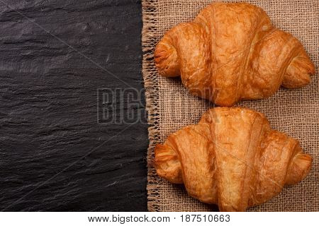 two croissant on black stone background with copy space for your text. Top view.