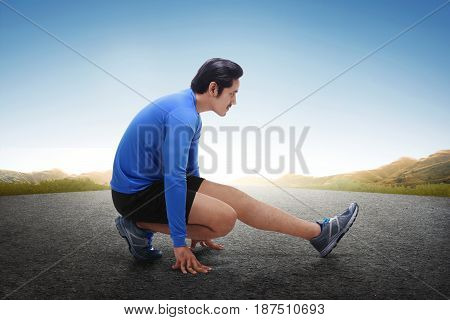 Young Asian Runner Stretching His Legs After Running Exercise